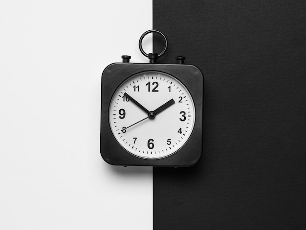 Orologio classico nero con quadrante bianco su sfondo bianco e nero. quadrante classico.