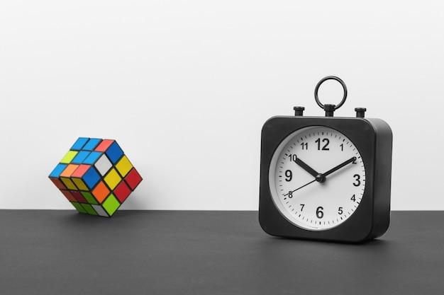 Orologio classico in bianco e nero e un cubo multicolore su sfondo bianco e nero. quadrante classico.