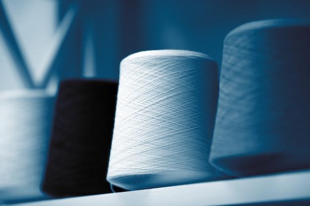 Fili blu classici, matasse e grovigli di filato di lana italiano, ferri da maglia.