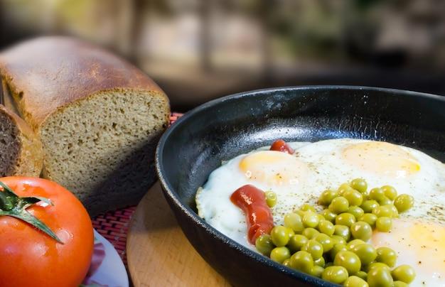Colazione classica uova fritte, piselli, pomodoro e pane su uno sfondo sfocato.
