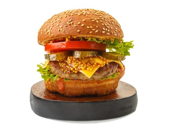 Hamburger classico con carne di manzo, verdure al formaggio in salsa con senape su un supporto rotondo di legno su uno sfondo bianco isolare la foto orizzontale