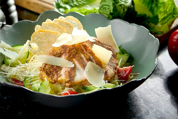 Classica insalata caesar con crostini di pane, parmigiano, pollo alla griglia, servita in una ciotola verde su un tavolo di marmo scuro. cibo del ristorante.