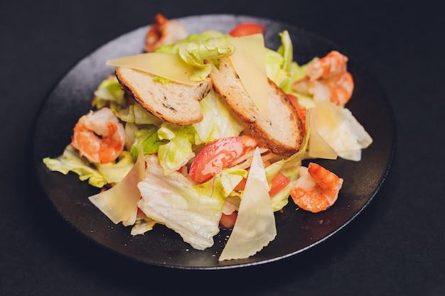 Classica insalata caesar con petto di pollo alla griglia e mezzo uovo in piatto di ceramica bianca. servito con ingredienti sopra sopra il vecchio fondo di legno blu scuro. vista dall'alto, spazio.