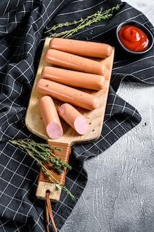 Salsicce di pollo classiche su un tagliere con rosmarino e spezie. sfondo nero. vista dall'alto