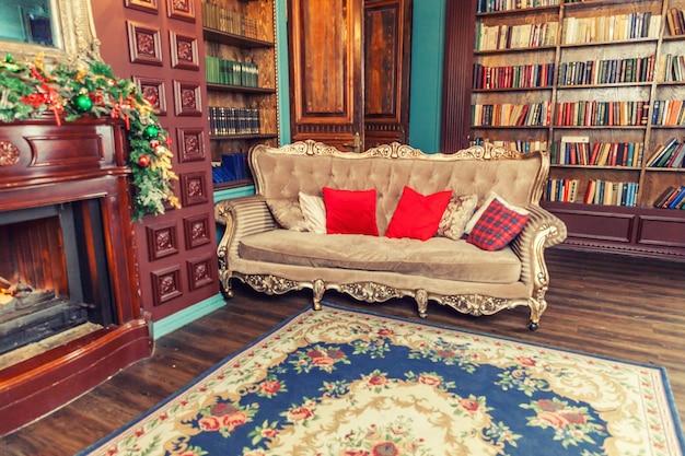 Il classico capodanno di natale ha decorato la biblioteca domestica della stanza interna con il camino. albero di natale con decorazioni di ornamento rosso. appartamento di design d'interni in stile classico moderno. la vigilia di natale in casa.