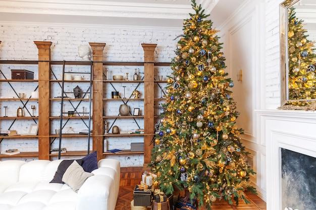 Natale classico capodanno decorato sala interna albero di capodanno. albero di natale con decorazioni ornamentali dorate. appartamento di design d'interni in stile classico bianco moderno. la vigilia di natale in casa.