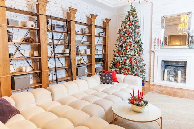 Natale classico capodanno decorato sala interna albero di capodanno. albero di natale con decorazioni d'argento e ornamenti rossi. appartamento di design d'interni in stile classico bianco moderno. vigilia di natale a casa