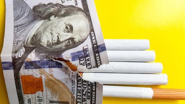 Le sigarette classiche stanno su banconote da cento dollari usa. sigarette su una banconota da cento dollari su uno sfondo giallo.