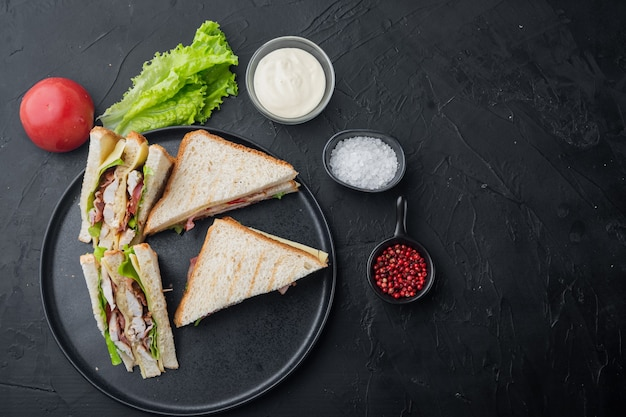 Classico club sandwich con carne, su sfondo nero, vista dall'alto con copia spazio per il testo