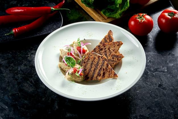 Piatto classico della cucina israeliana - forshmak di aringhe con crostini di pane servito in un piatto bianco su un tavolo di marmo. frutti di mare.