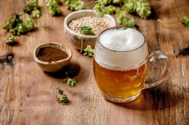 Classico boccale di vetro di birra chiara schiumosa fredda fresca con coni di luppolo verde, chicco di grano e malto rosso fermentato in ciotole di ceramica dietro sopra un tavolo di legno. copia spazio