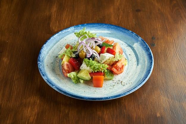Insalata greca classica con pomodori, cetrioli, cipolle rosse, formaggio feta e olive, servita in un piatto blu su una superficie di legno