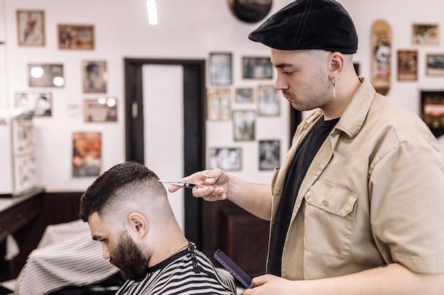 Taglio di capelli classico in un barbiere. curva lo styling dei capelli e l'assistenza sanitaria dei capelli in un negozio di barbiere. taglio di capelli da uomo.