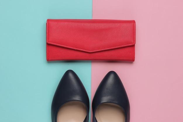 Scarpe classiche con tacco alto, portafoglio in pelle rossa su rosa pastello blu.