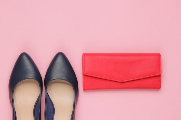 Scarpe classiche con tacco alto, portafoglio in pelle rossa su rosa.