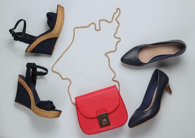 Scarpe classiche con tacco alto, sandali con plateau, borsa in pelle rossa su fondo bianco