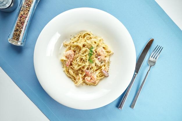 Classica pasta italiana fatta in casa (spaghetti) in salsa di formaggio con gamberi e frutti di mare in un piatto bianco sulla tovaglia blu