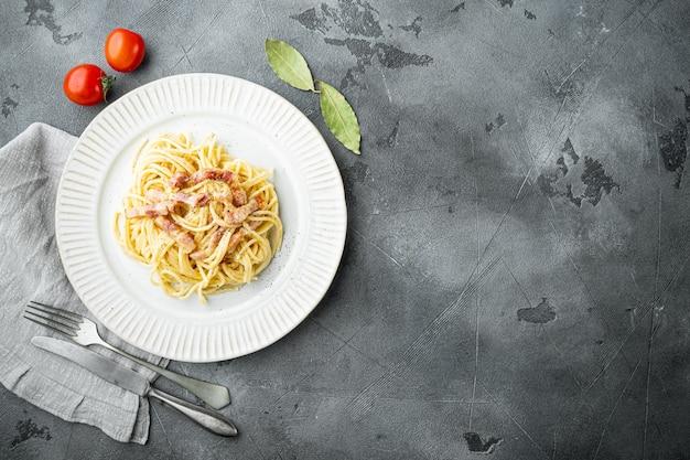 Classica pasta fatta in casa alla carbonara italiana con pancetta, uova, parmigiano, set di pietra grigia sul tavolo, vista dall'alto laici piatta, con spazio di copia