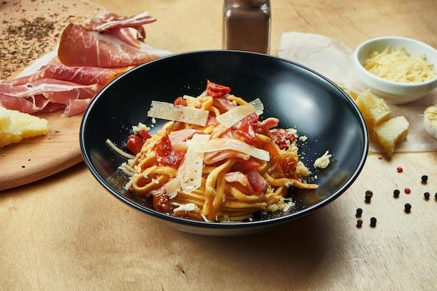 Pasta classica fatta in casa con salsa rossa, parmigiano, prosciutto e pomodori secchi in ciotola nera. cucina italiana tradizionale