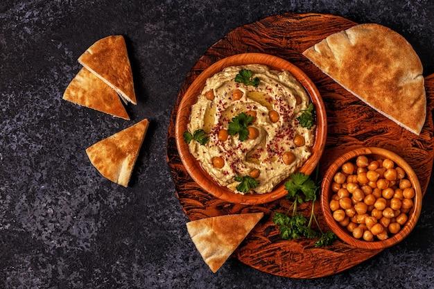 Hummus classico con prezzemolo nel piatto e pane pita.