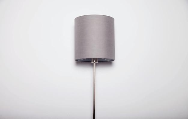 Lampada classica illuminata grigia con paralume contro il muro bianco