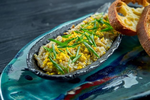 Un classico piatto israeliano è il forshmak di aringhe in un piatto blu, servito con crostini di pane su una superficie di legno scuro. vista ravvicinata su vorschmack o forshmak