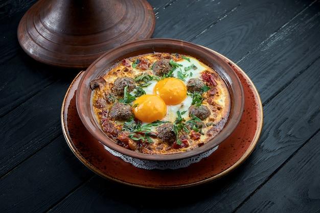 Classiche uova strapazzate israeliane - shakshuka con pomodori, erbe aromatiche e spiedini di carne, servite in un piatto di argilla su una superficie nera