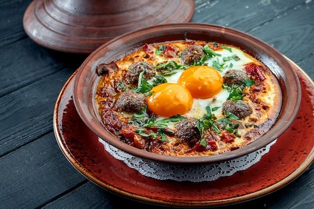 Classiche uova strapazzate israeliane - shakshuka con pomodori, erbe e spiedini di carne, servite in un piatto di argilla su una superficie nera.