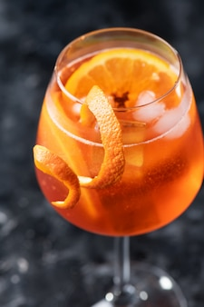 Cocktail italiano classico dello spritz dell'aperol in vetro su un buio, fine su