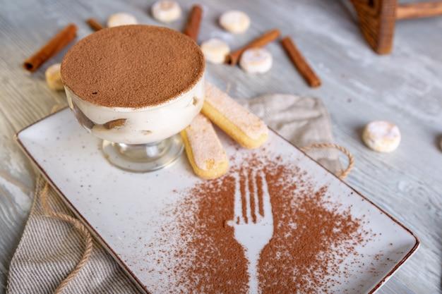 Un classico tiramisù dolce italiano in una ciotola con una porzione atmosferica di tè.
