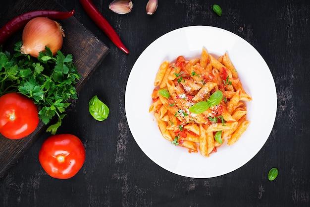 Classica pasta italiana penne alla arrabiata con basilico e parmigiano grattugiato fresco sul tavolo scuro. penne al sugo di peperoncino all'arrabbiata. vista dall'alto, sopra, copia spazio