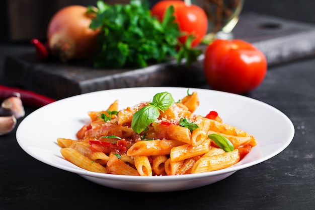 Classica pasta italiana penne alla arrabiata con basilico e parmigiano grattugiato fresco sul tavolo scuro. penne al sugo di peperoncino all'arrabbiata.