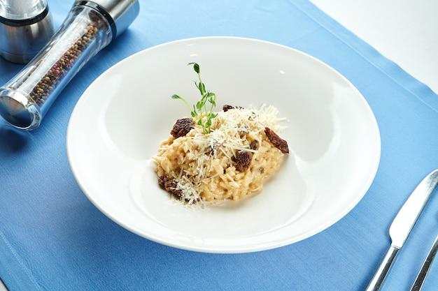 Risotto italiano classico con tartufo e pomodori secchi, parmigiano in un piatto bianco su una tovaglia blu.