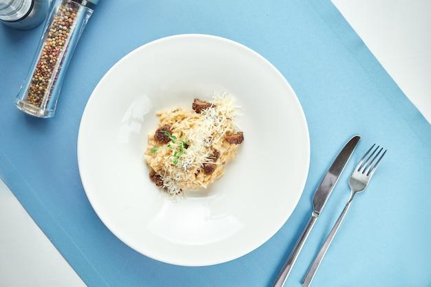Risotto italiano classico con tartufo e pomodori secchi, parmigiano in un piatto bianco su tovaglia blu.