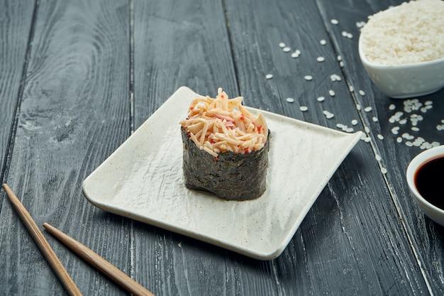 Rotoli di sushi giapponesi classici - gunkan con il granchio e la salsa bianca piccante su un piatto ceramico bianco su un fondo di legno nero. avvicinamento