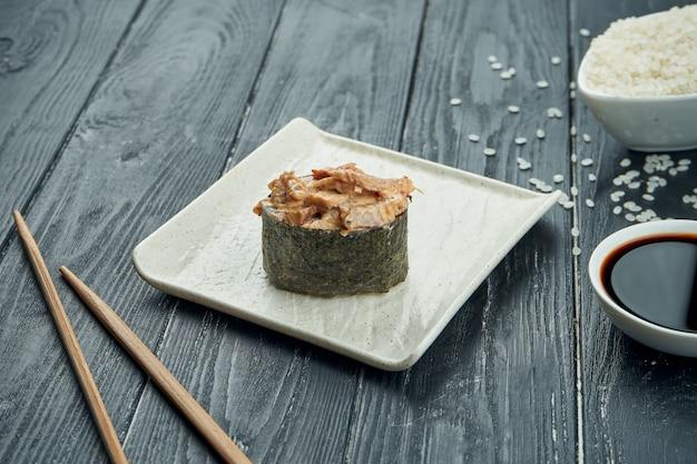 Rotoli di sushi giapponesi classici - gunkan con l'anguilla e la salsa bianca piccante su un piatto ceramico bianco su un fondo di legno nero. avvicinamento