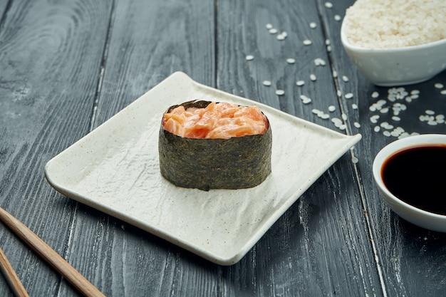 Rotoli di sushi giapponesi classici - gunkan con salmone e salsa bianca piccante su un piatto ceramico bianco su un fondo di legno nero. avvicinamento