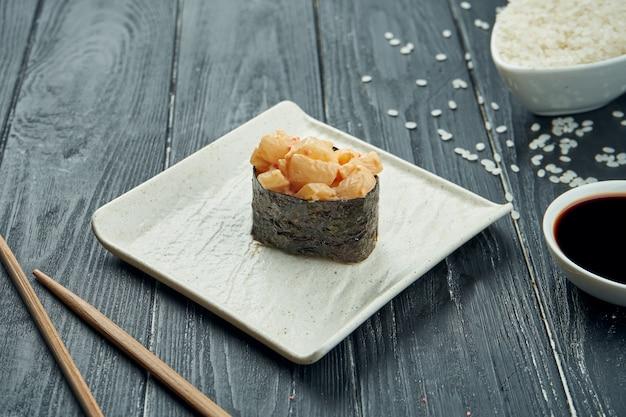 Rotoli di sushi giapponesi classici - gunkan con scaloppina e salsa bianca piccante su un piatto ceramico bianco su un fondo di legno nero. avvicinamento