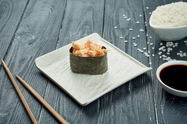 Rotoli di sushi giapponesi classici - gunkan con gamberetto e salsa bianca piccante su un piatto ceramico bianco su un fondo di legno nero. avvicinamento