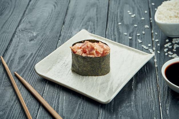 Rotoli di sushi giapponesi classici - gunkan con il tonno e la salsa bianca piccante su un piatto ceramico bianco su un fondo di legno nero. avvicinamento