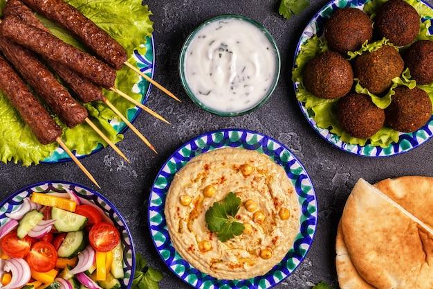 Spiedini classici, falafel e hummus nei piatti