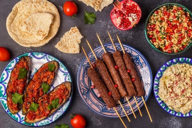 Spiedini classici, insalata tabbouleh, babà ganush e melanzane al forno con salsa. piatto tradizionale mediorientale o arabo. vista dall'alto.