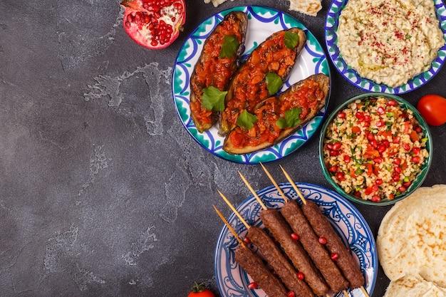Spiedini classici, insalata di tabulé, babà ganush e melanzane al forno con salsa.