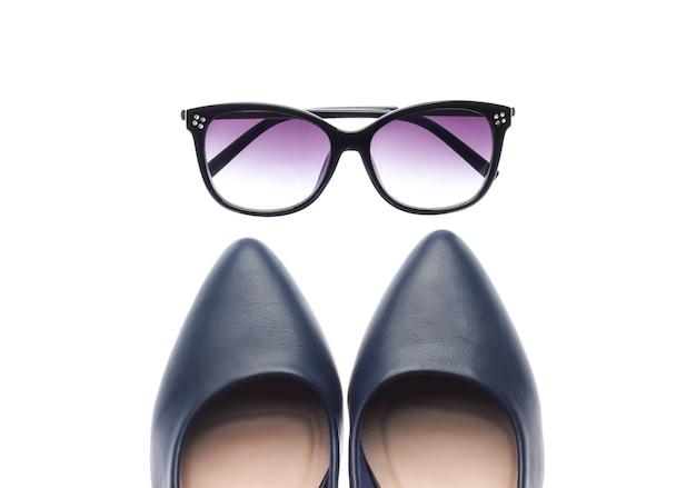 Scarpe tacco alto in pelle classica e occhiali da sole isolati su priorità bassa bianca. accessori da donna
