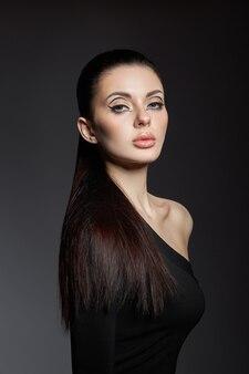 Trucco classico sul viso di donna, bellissimi occhi grandi. moda trucco perfetto, occhi espressivi sul viso della ragazza, sopracciglia nere lisce, capelli castani leccati. ritratto di donna su sfondo scuro