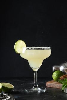 Cocktail classico di margarita con lime e cubetto di ghiaccio su sfondo nero freschezza alcolica estiva freshness