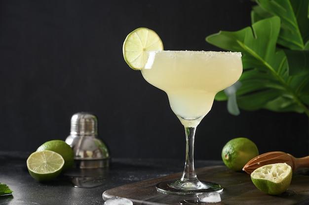 Cocktail classico di margarita con succo di lime e cubetto di ghiaccio su sfondo nero con splash