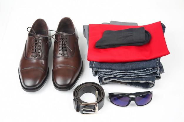 Scarpe da uomo classiche, cintura, occhiali e vestiti su sfondo bianco