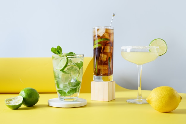 Mojito classico, cuba libre, cocktail margarita con lime e limone su sfondo giallo di colore moderno. tre bevande fresche estive per feste. aperitivo festivo.