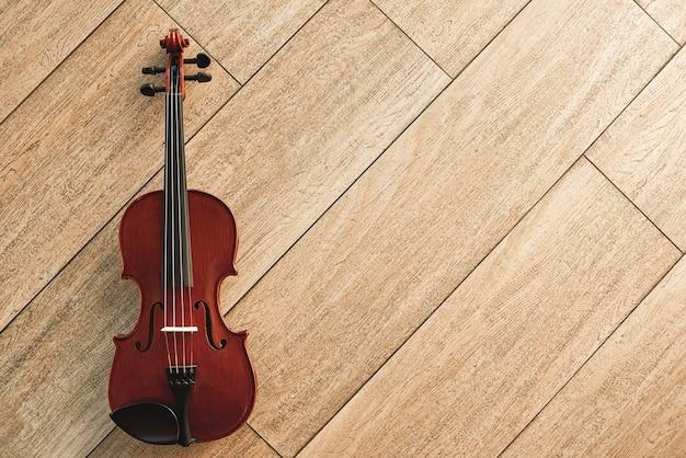 Strumento musicale classico. vista dall'alto del violino marrone sdraiato sul pavimento in legno chiaro. strumenti musicali. apparecchiature musicali. musica di sottofondo